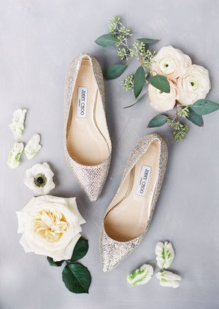 glitter metallic jimmy choo heels with ranunculus and anemone garden rose flowers detail shot photo