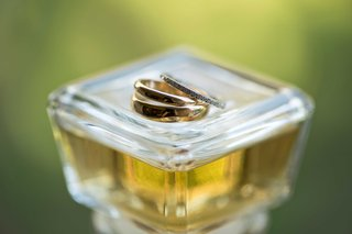 mens-and-womens-gold-silver-wedding-rings-with-jewels-on-top-of-perfume-liquor-bottle