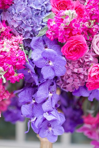 wedding-reception-centerpiece-of-purple-vanda-orchids-hydrangeas-hot-pink-roses