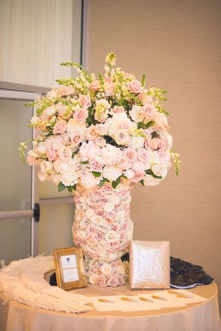 welcome-table-at-a-jewish-wedding-ceremony-with-vase-covered-in-pale-purple-orange-white-roses