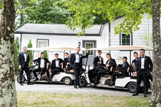 groom-and-groomsmen-before-wedding-ceremony-on-large-golf-carts-at-summer-camp-theme-wedding-weekend