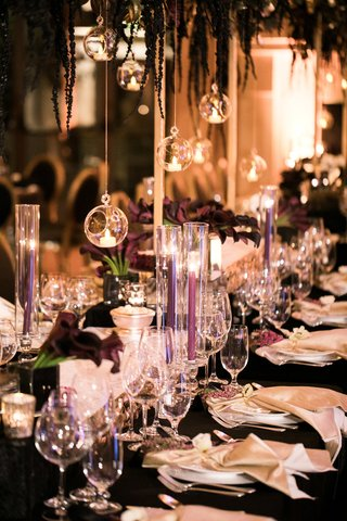 wedding-reception-with-darker-colors-purple-tapered-candles-black-linens-glass-globes
