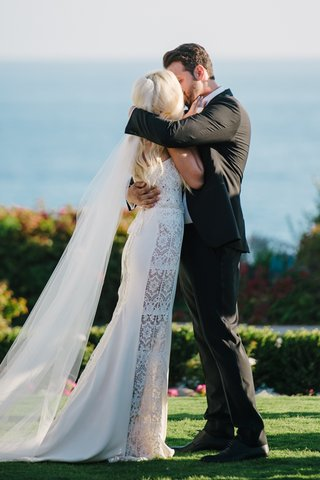 groom-in-black-tux-kisses-bride-in-a-galia-lahav-dress-with-lace-panels-veil-at-ceremony