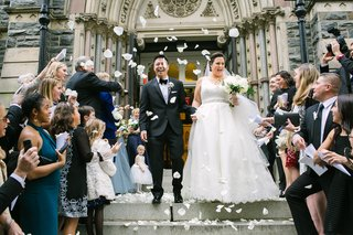 wedding-ceremony-at-catholic-church-bride-and-groom-on-stairs-with-flower-petals-getaway-car
