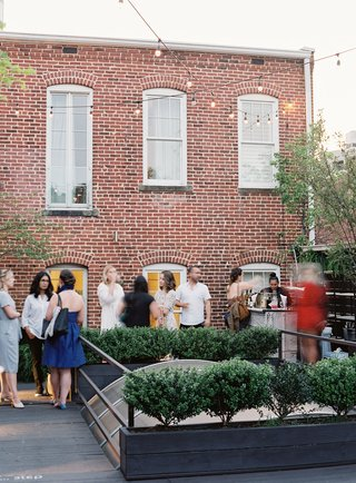 wedding-event-guests-on-washington-dc-rooftop-gallery-venue-brick-wall-atrium-glass-hedge-wall