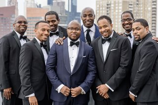 groom-in-navy-tuxedo-jacket-with-bow-tie-and-groomsmen-family-in-tuxedos-black-white