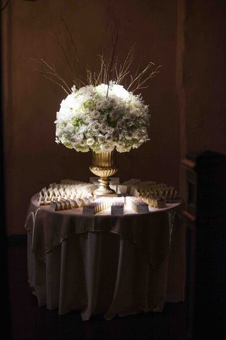 wedding-place-card-table-with-a-large-golden-urn-with-white-flowers