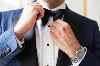 groom-with-navy-suit-white-shirt-black-buttons-black-bow-tie-movado-watch