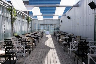 a-semi-open-ceremony-space-on-rooftop-with-white-concept-foliage-alternating-black-and-white-chairs