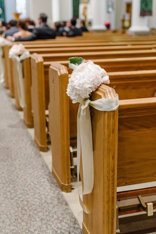 wedding-ceremony-at-church-catholic-couple-flowers-and-ribbon-on-some-church-pews-wood-pew