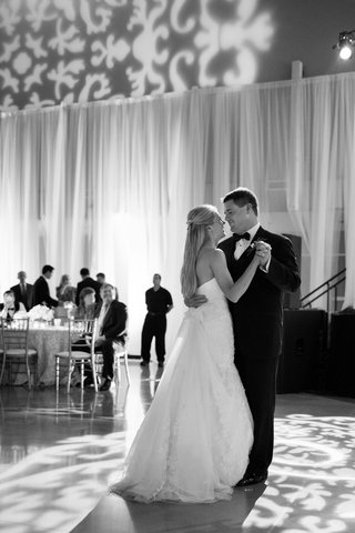 black-and-white-photo-of-bride-in-a-strapless-gown-dancing-with-groom-in-a-tuxedo