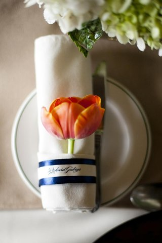 rolled-napkins-wrapped-in-blue-ribbon-and-tulip