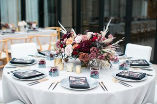 round-table-with-centerpiece-of-burgundy-and-mauve-roses-with-pampas-grass