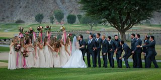 fun-bridesmaid-and-groomsmen-photo-with-bouquets-on-golf-course-at-la-quinta-resort-and-club