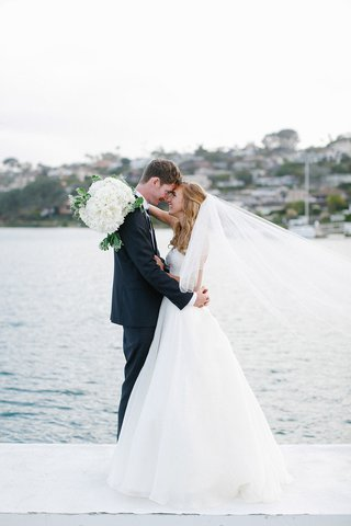 bride-in-white-wedding-dress-and-groom-in-tuxedo-embrace-on-pier-in-san-diego