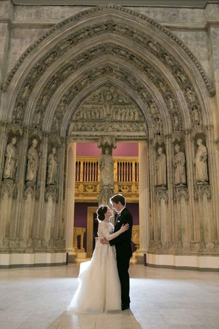 newlyweds-embracing-roman-catholic-church-pittsburgh-pa-liancarlo-wedding-dress-religious-ceremony