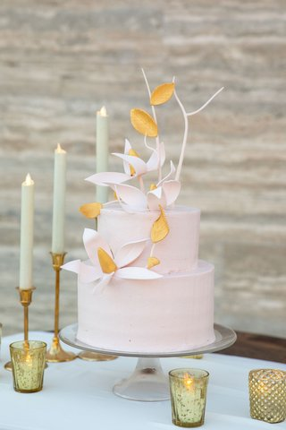 wedding-cake-on-glass-cake-stand-two-layer-round-cake-pink-with-sugar-flowers-branches-gold-taper