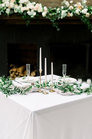 square-reception-table-with-three-tapered-candles-of-varying-heights-and-greenery-garland