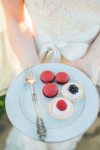 bride-holding-plate-of-red-french-macarons-fruit-tarts-desserts-on-white-china