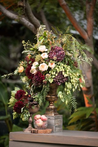 wedding-reception-wood-bar-with-bowl-of-peaches-and-centerpiece-with-greenery-burgundy-flowers