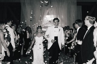black-and-white-photo-of-bride-and-groom-in-white-tuxedo-jacket-walk-away-from-reception-toss