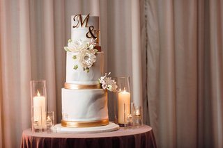 three-tier-wedding-cake-with-marble-frosting-and-copper-accents