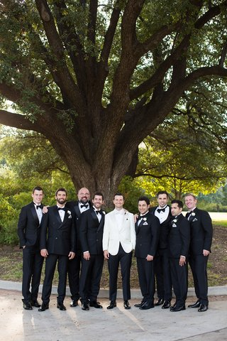 groom-in-black-pants-and-white-tuxedo-bow-tie-with-groomsmen-in-traditional-tuxedos