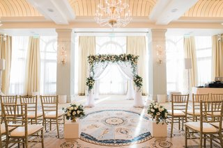 indoor-ceremony-with-arch-of-greenery-and-white-flowers-white-drapery