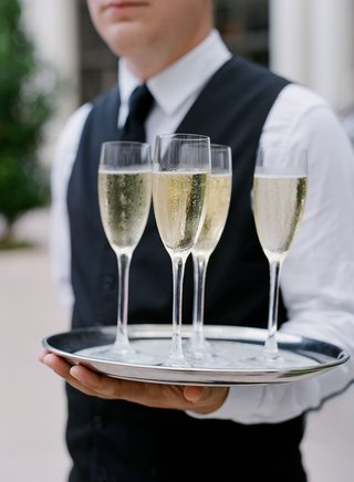 wedding-reception-cocktail-hour-silver-tray-four-glasses-of-champagne-vest-server