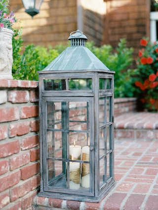 rustic-large-lantern-on-brick-steps-with-candlelight-coming-from-white-candles-wrapped-in-gold