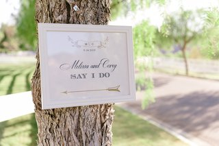 directional-sign-with-the-couples-names-initials-and-arrow-for-outdoor-ceremony-posted-on-tree