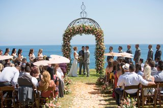 bride-in-ines-di-santo-wedding-dress-under-ceremony-arch-guests-with-parasols-sunny-summer-wedding