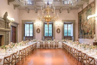 wedding-reception-villa-ballroom-u-shape-table-low-centerpieces-tapestry-chandelier-vineyard-chairs