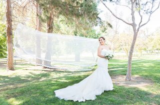 brides-veil-flowing-in-wind-long-chapel-length-catholic-wedding-park-pictures-california