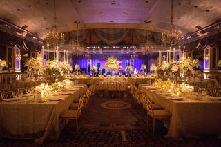 reception-with-white-tablescapes-with-long-tables-tall-floral-arrangements-candles-purple-uplighting