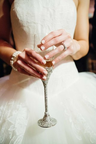 bride-with-engagement-ring-and-pearl-bracelet-holding-sparkling-crystal-champagne-flute