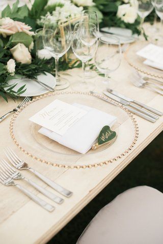 wedding-reception-light-wood-table-gold-clear-charger-menu-in-napkin-green-leaf-gold-calligraphy