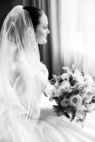 black-and-white-photo-of-bride-in-wedding-dress-with-veil-over-updo-looking-out-window-with-bouquet