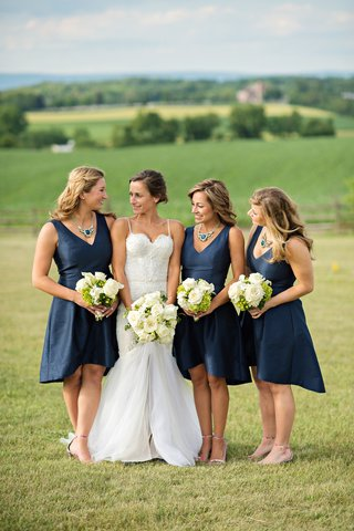 bride-in-a-berta-bridal-gown-with-bridesmaids-in-sleeveless-navy-dresses-necklaces-with-blue-stones