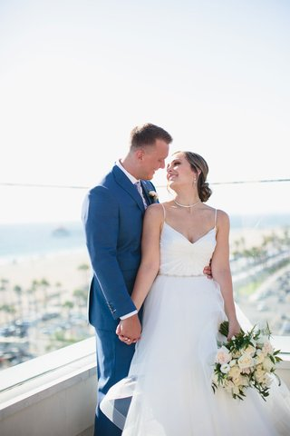 bride-in-v-neck-spaghetti-strap-wedding-dress-groom-in-blue-suit-on-balcony-overlooking-beach-ocean