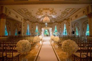 wedding-ceremony-custom-white-and-gold-border-aisle-runner-ballroom-ornate-white-flowers-gold-chairs