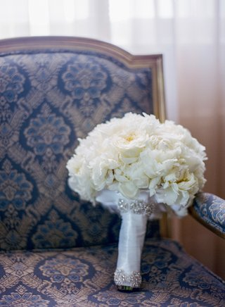 white-bridal-bouquet-with-crystal-and-satin-wrap-on-chair