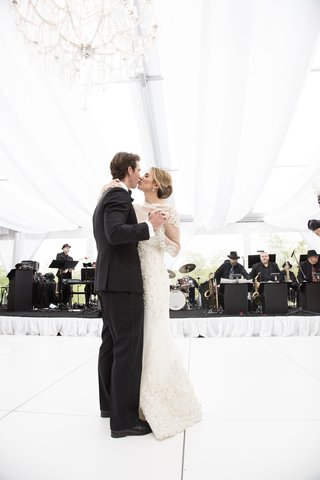 bride-groom-kiss-while-dancing-wedding-reception-all-white-black-tux-love-newlyweds