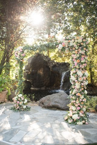 wedding-ceremony-arch-with-pond-and-waterfall-backdrop-greenery-white-hydrangea-pink-orange-roses