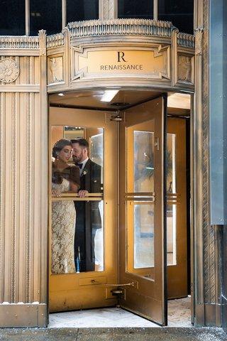 bride-with-fur-bolero-and-groom-in-tuxedo-at-renaissance-hotel-revolving-gold-door