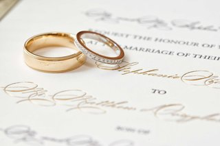 gold-polished-mens-wedding-band-ring-and-womens-gold-ring-with-diamond-pave-details-on-invitation