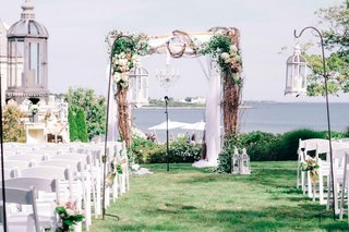 an-arbor-with-winding-branches-foliage-and-white-flowers-in-front-of-view-of-bay
