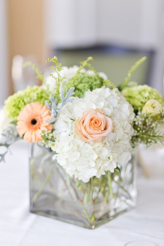 wedding-reception-centerpiece-of-white-hydrangea-pastel-orange-gerbera-daisy-greenery