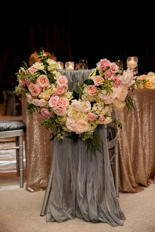 grey-fabric-draped-over-brides-chair-with-flower-garland-at-gold-sequin-sweetheart-table