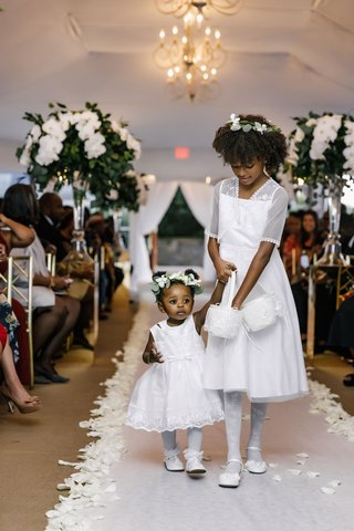two-flower-girls-in-white-dresses-with-baskets-and-greenery-white-flower-crowns-white-aisle-petals